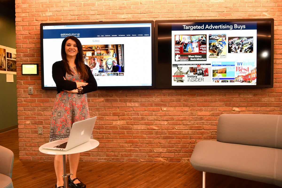 Rita Colistra standing in front of two large television screens.