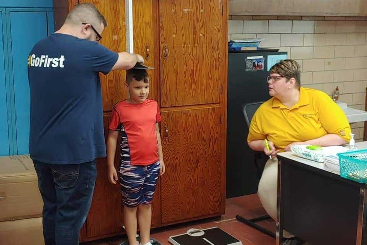 boy is measured for height while one adult helps, another watches
