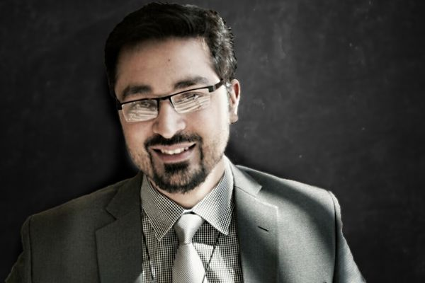 photo of man with dark hair, glasses, wearing gray suit, lighter gray shirt, tie.