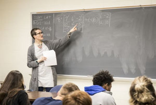 Woman with short hair and glasses teaches math to a classroom of students
