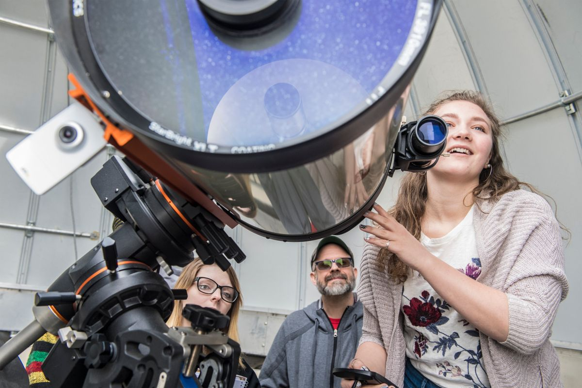 people look through a large telescope