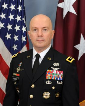 A bald man in uniform with several service medals in front of the American Flag