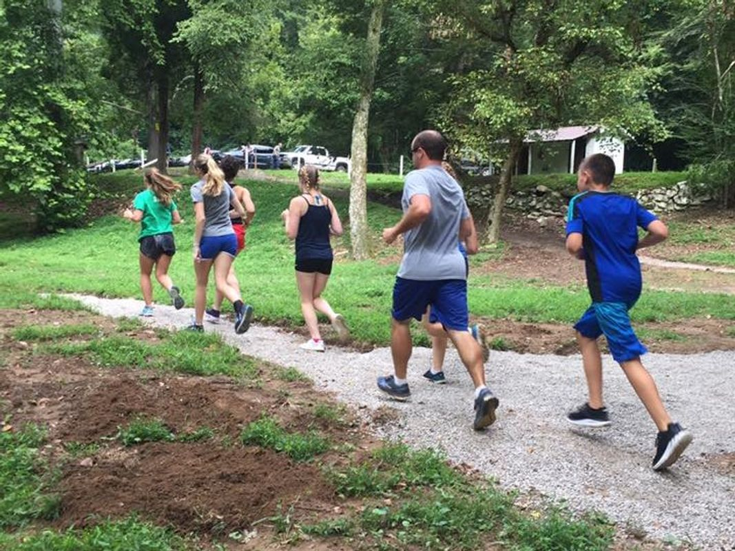 Seven people on a run through a wooded area.