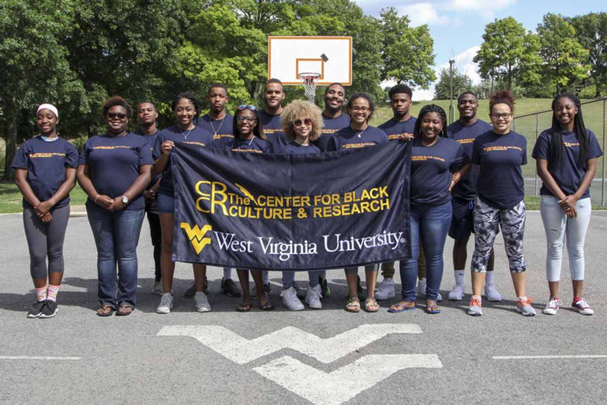 Members of WVU Academic STAR program hold a banner which reads