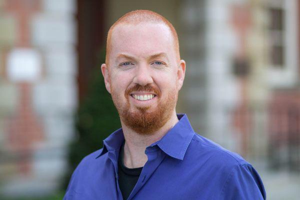 photo of smiling man in royal blue shirt