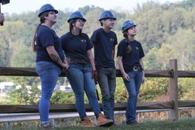 group of young men and women lean on a wooden fence in matching hard hats and t-shirts