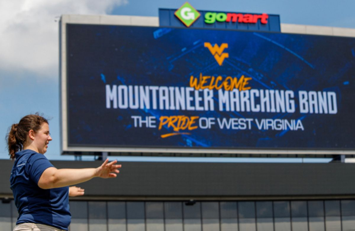 A girl's profile standing all the way to the left with a huge WVU Mountaineer Marching Band billboard in the background