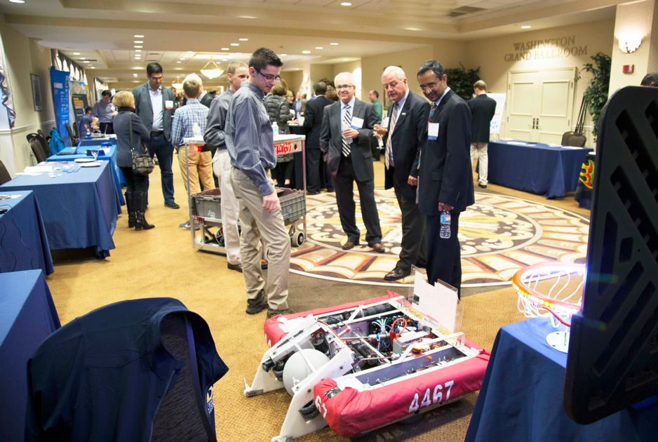 Four people look at a robot during an indoor event