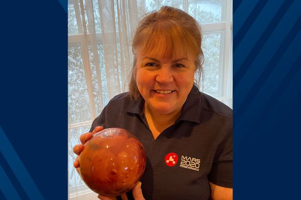 smiling woman holding Mars planet model