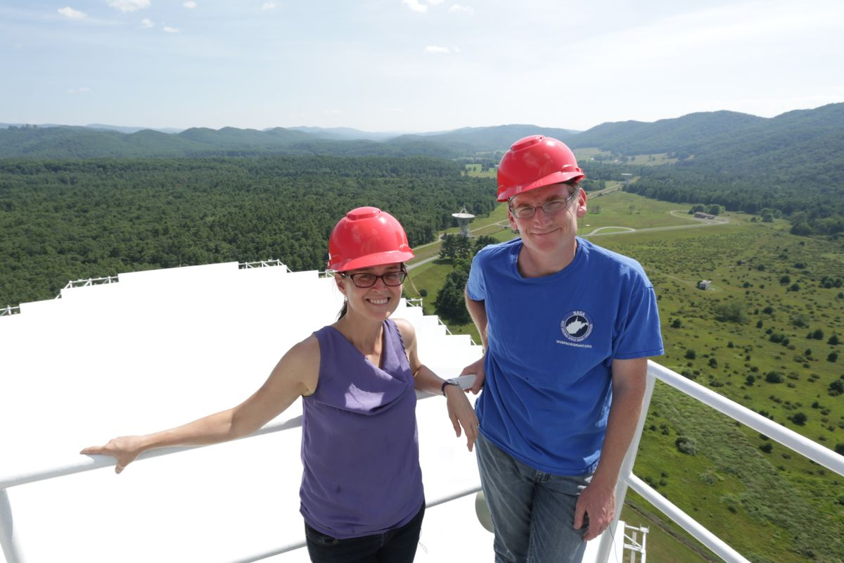 (Left) A woman in a purple tank top and a red hard hat and (Right) a man in a blue t shirt and a red hard hat pose on a gate in front of mountains.