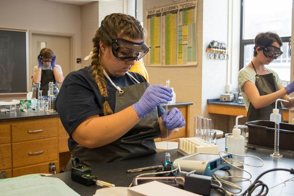 girl in braids in lab wearing purple gloves, goggles
