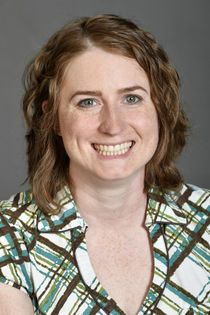 Headshot of woman smiling with brown hair and green and brown plaid shirt