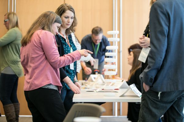 Two women point to an exhibit on a table during Leap into Science training