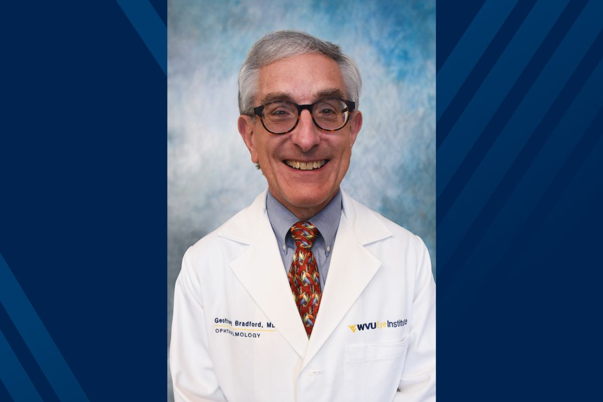 smiling man with glasses wearing a white doctor's coat