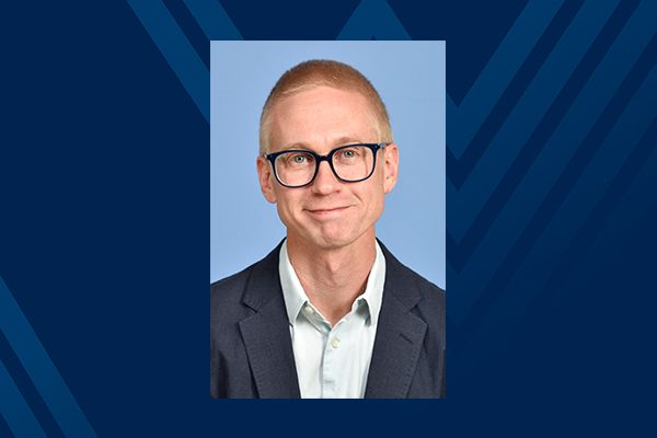 Smiling man with glasses on blue background
