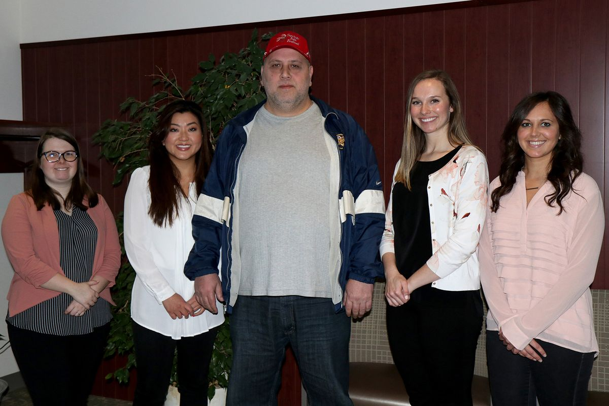 Four female WVU law students standing with man in grey shirt and red hat