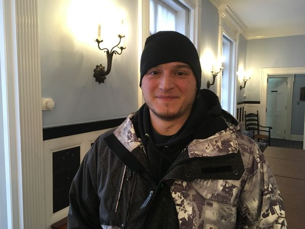 Man in two-toned jacket and black beanie smiles for a picture.