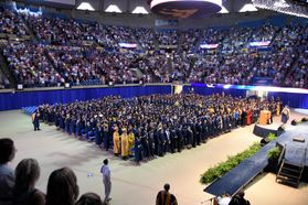 Students stand at graduation ceremonies