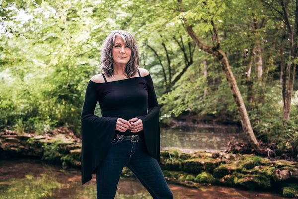 photo of woman in black top standing next to stream with trees in background