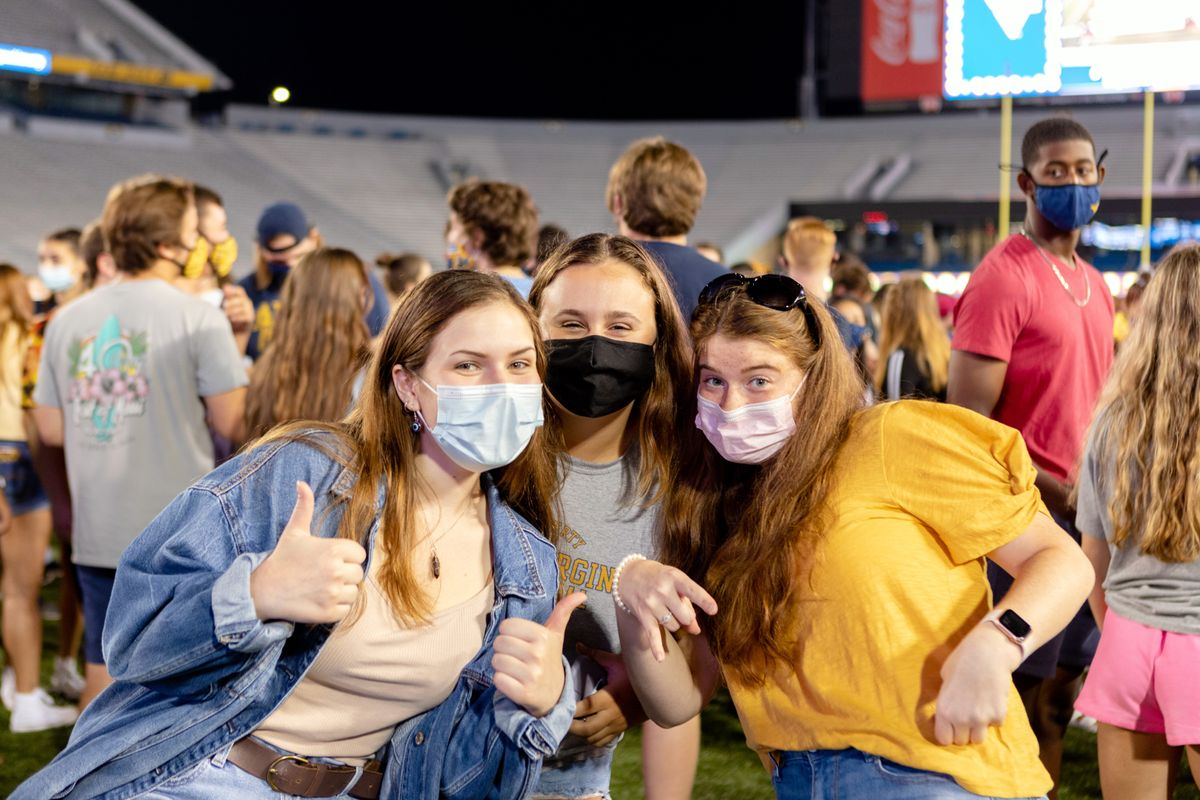 Three girls wearing masks stand on the football field and pose for a picture.