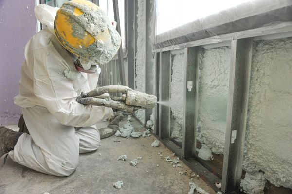 person in hardhat, white coveralls, sprays insulation in exposed walls