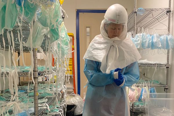 woman in protective gear in a room with masks