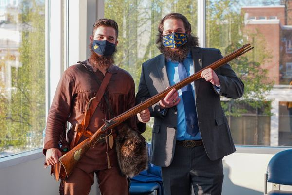 man in buckskins stands next to a man in a suit and tie as both hold a musket