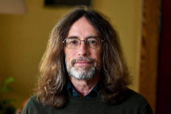 smiling man with long hair, beard