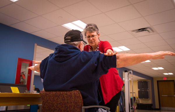 Woman helps man in hat with stretching his arms