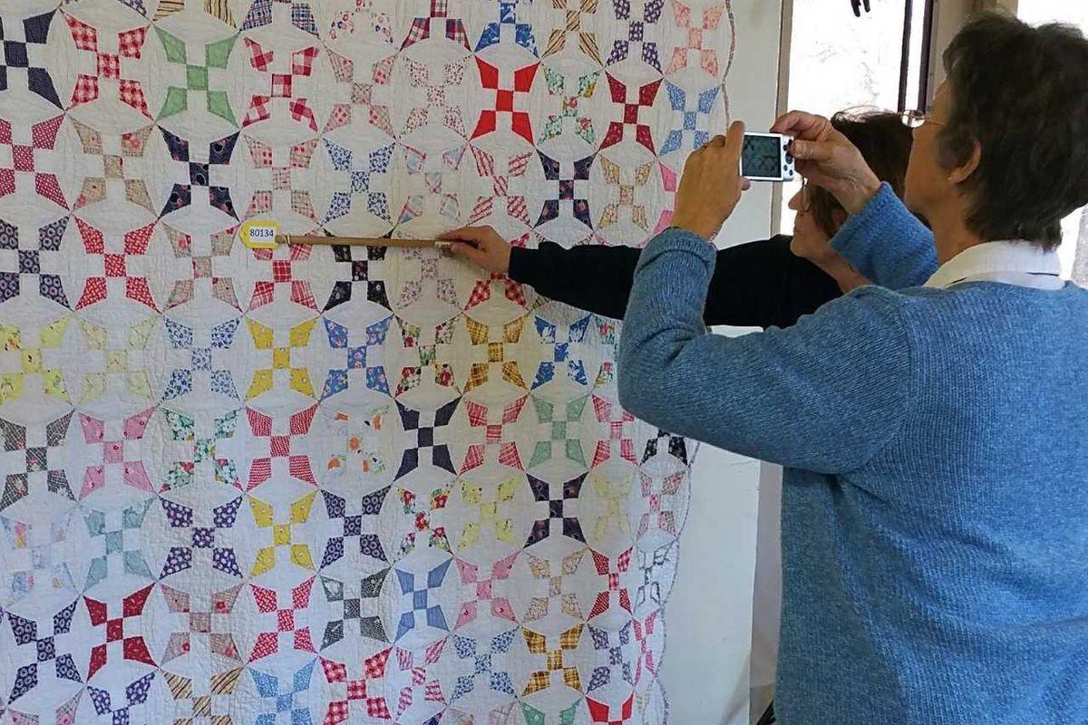 A woman photographs a quilt
