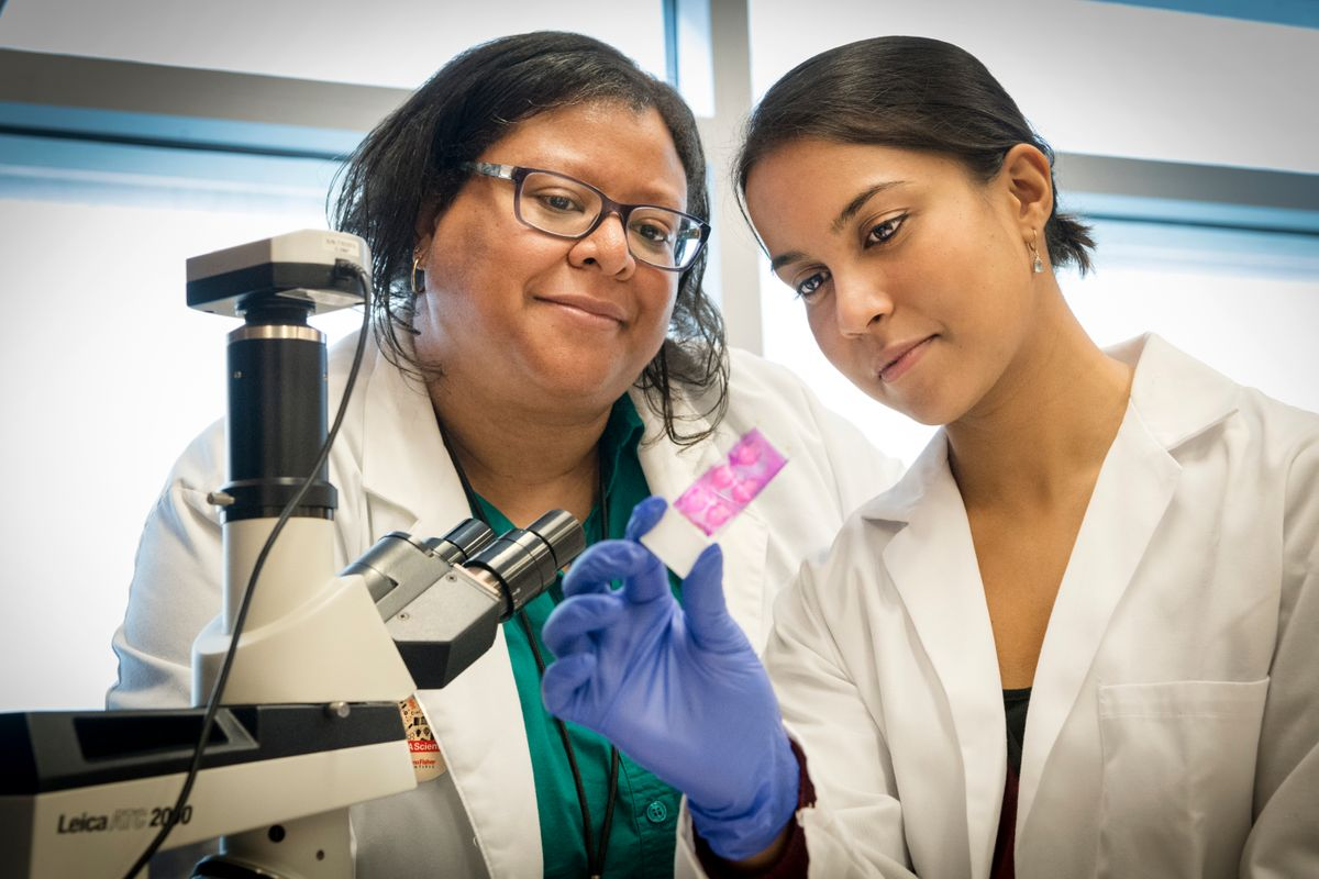 Two women standing next to a microscope, looking at a slide