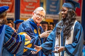 Easter Kith, exercise physiology major in the School of Medicine, is congratulated by Provost and Vice President for Academic Affairs Joyce McConnell as she walks across the platform during December Commencement in the Coliseum Dec. 15, 2018.