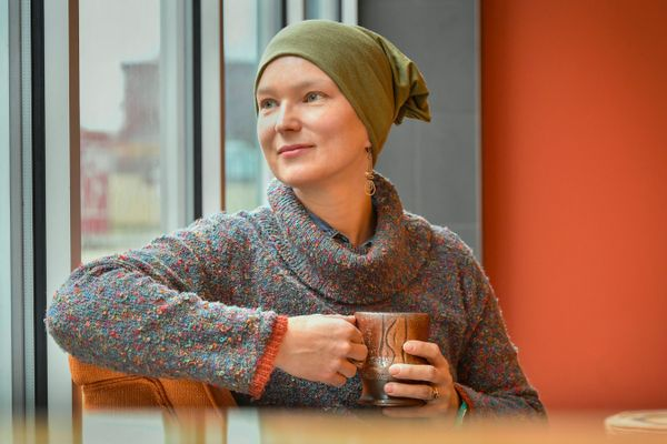 A woman with a mug wearing a scarf to cover her head looks out a window