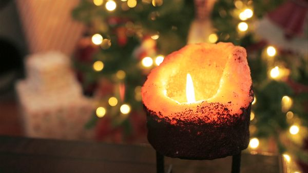 Close-up of a lit candle in front of a Christmas tree.