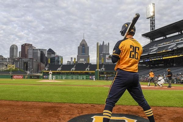 man holding baseball bat in baseball stadium