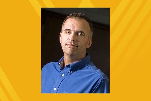 Portrait of a man in a blue shirt on a gold background
