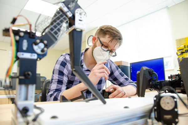 man with glasses, mask, works at robotic arm station