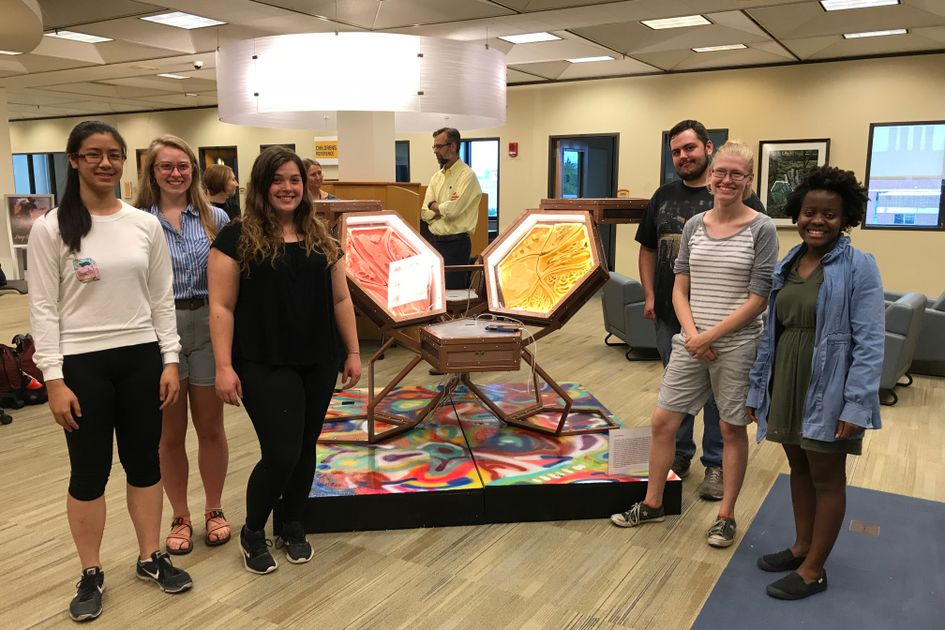 Six students stand with a sculpture