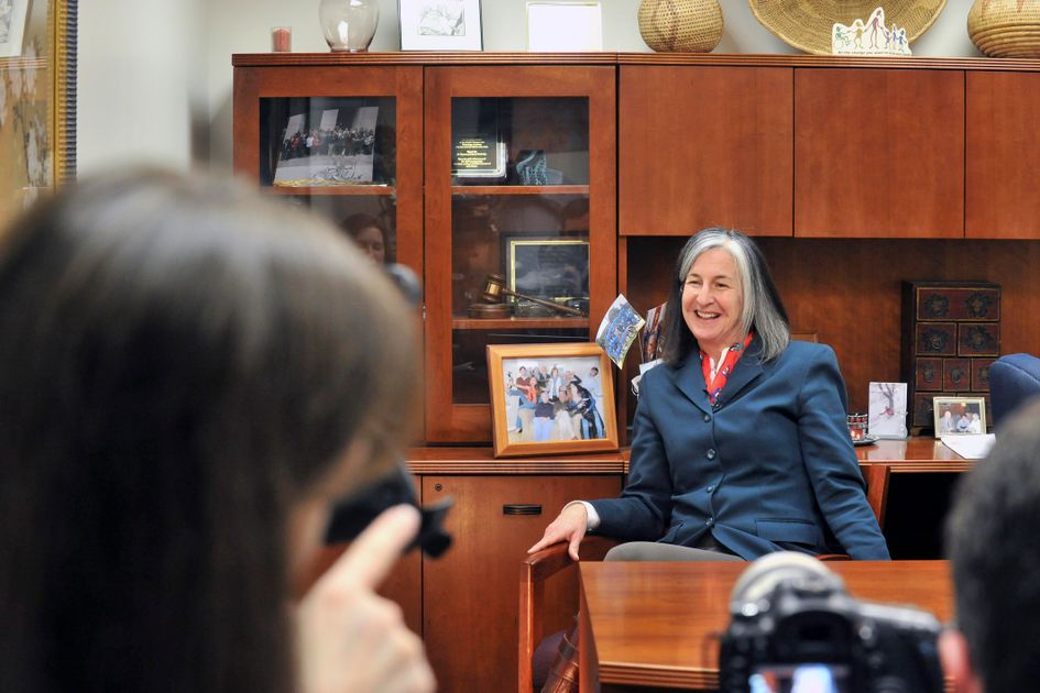 Ann Chester is photographed in front of a desk