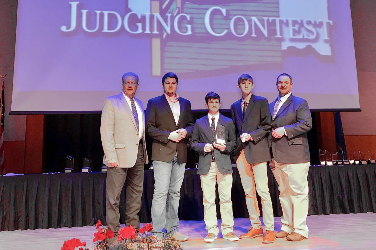 boys and men stand on a stage during an awards ceremony