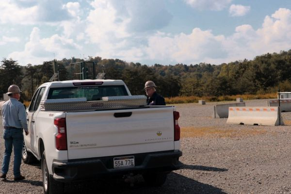 two men stand at doors of white pickup truck on graveled ground with concrete barriers in the background