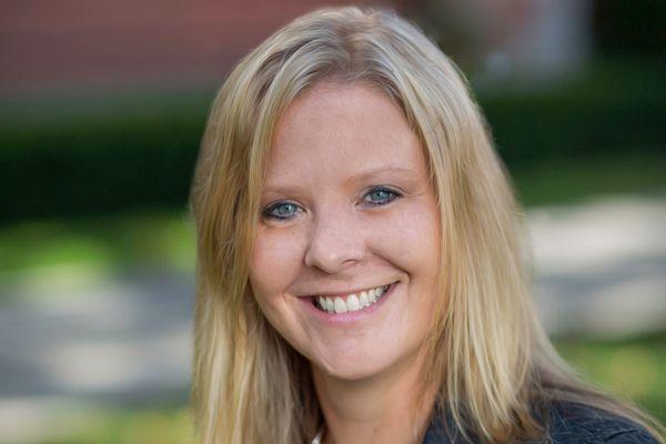 blonde woman smiling, shoulder-length hair