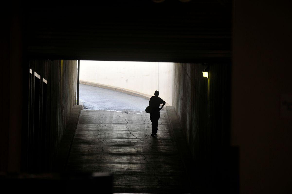 A person walks in a dark tunnel toward light