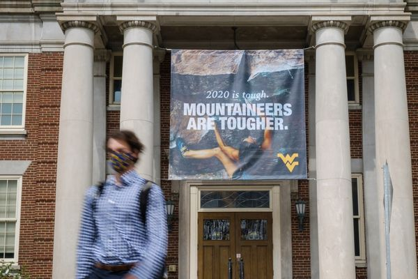 person walks out of building with banner that says Mountaineers are tougher