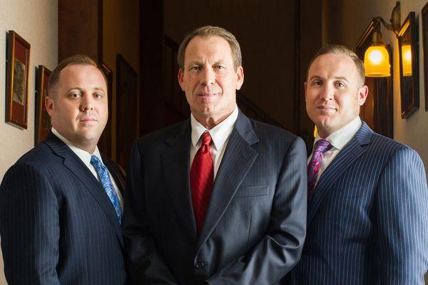 Three men pose in suits