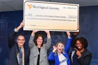 Four people hold a large check over their heads in celebration