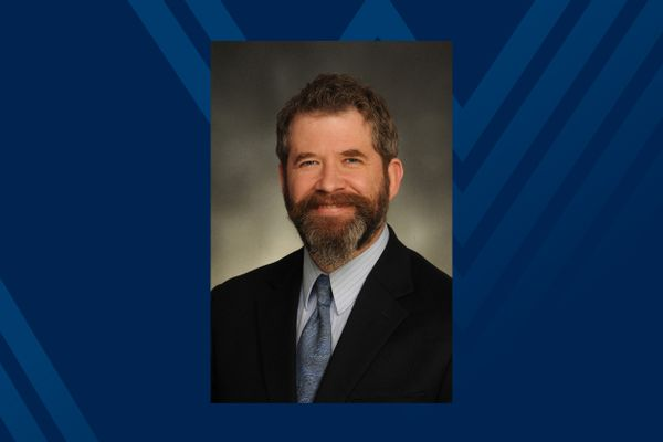 photo of smiling man with beard in suit and tie on blue background