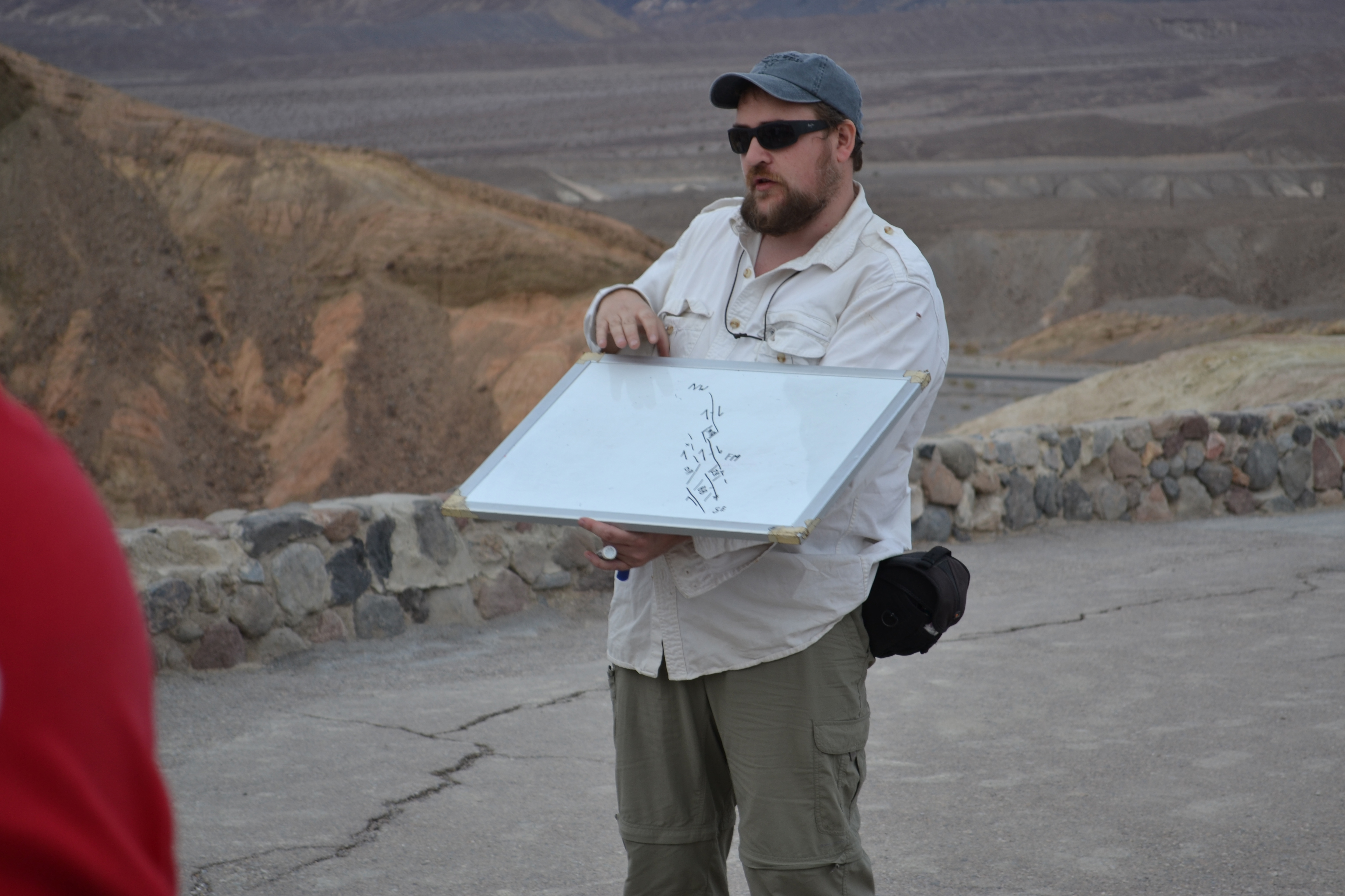 Photo of a man wearing a cap and sunglasses holding a chart