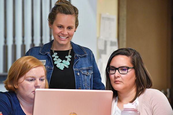 three women looking at pink laptop