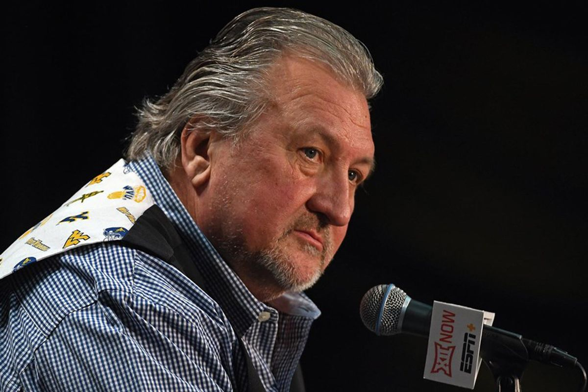 man with gray hair, beard stares overtop of microphone